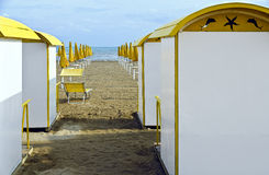 Bathing huts and closed yellow sun umbrellas. Yellow-white bathing huts and closed yellow sun umbrellas on the sand beach of the Adriatic sea at Grado, Italy Royalty Free Stock Images