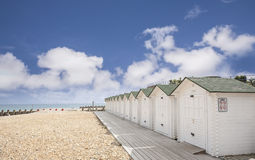 Bathing Huts at Eastbourne, East Sussex. Bathing huts on the beach at Eastbourne, East Sussex, England, under a beautiful early summer sky stock images