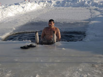 Bathing in an ice-hole. The man is dipped into an ice-hole. Winter. Day Stock Photo