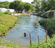 Bathing and medical treatment in a natural spa. People practicing and enjoying a natural spa and alternative medical treatment in a local river near Knjazevac stock photo
