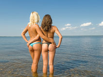 Bathing season. Two girls sunbathing on the beach royalty free stock photos