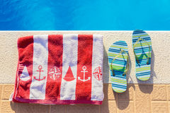 Bathing slippers and bath towel at swimming pool. Bathing slippers and bath towel at blue swimming pool in summer royalty free stock image