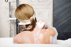 Bathing woman cleaning her back with soap. Stock Photography