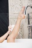 Bathing woman cleaning her leg with sponge. Stock Photo