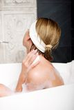 Bathing woman cleaning herself with soap. Royalty Free Stock Photos