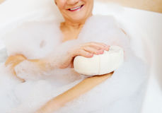 Bathing woman relaxing with sponge Stock Images