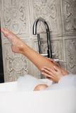 Bathing woman's leg in bath. Royalty Free Stock Photography