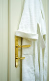 Bathrobe. A white bathrobe hangs from the door in a luxury hotel royalty free stock photo