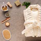 Bathrobe bath soap and loofah, herbs on a stone. Background Royalty Free Stock Images