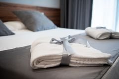 Bathrobe on bed in hotel room. Bathrobe on bed in a bright hotel room royalty free stock images