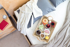 Bathrobe and Breakfast Tray on Unmade Bed Stock Images
