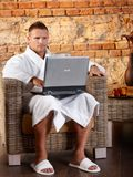Bathrobe man with laptop in armchair Stock Photo
