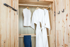 Bathrobe and shirt, pants in wooden wardrobe Royalty Free Stock Photo