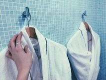 Bathrobe white in a hotel bathroom hand touches one. Bathrobe white in a hotel bathroom indoor Royalty Free Stock Photo