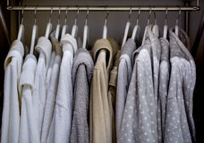 Bathrobes with hangers in wardrobe Royalty Free Stock Images