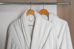 Bathrobes hanging in wardrobe royalty free stock photography