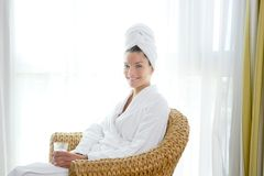 Bathrobl woman sitting relaxed hold glass of water Royalty Free Stock Images