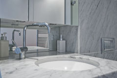 Bathroom. Modern bathroom with bath tub, toilet and hand wash basin with light marble finish Royalty Free Stock Photo