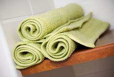 Bathroom. Three green and clean towels rolled in bathroom Stock Photography