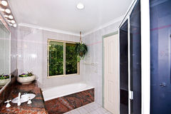 Bathroom. This is a photo of a bathroom with granite bench tops and bath edging Stock Images