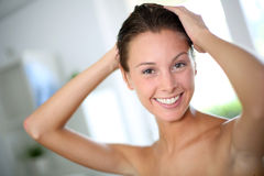 In the bathroom. Portrait of beautiful woman putting her hair up Stock Photo