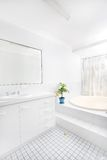 Bathroom. Brightly lit airy bathroom with white tiles royalty free stock images