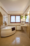 Bathroom. Beige bathroom with big bath and window Royalty Free Stock Photos