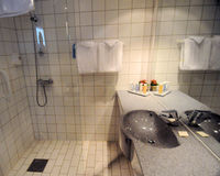 Bathroom. A bathroom with a shower stall, sink, counter and toiletries Stock Images