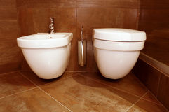 Bathroom. A white toilet and bide is in a bathroom Royalty Free Stock Image