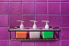 Bathroom Accessories. Colorful bottles that contain liquid soap, shampoo and hair conditioner in purple decorated tiling bathroom Royalty Free Stock Photos