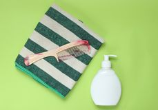 Bathroom accessories. On green background. Towel, hairbrush, bottle shampoo. Hair care. Top view stock photo