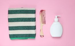 Bathroom accessories. On pink background. Towel, hairbrush, bottle shampoo. Hair care. Top view royalty free stock image