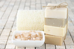 Bathroom accessories. Stack of various natural soaps, bath salt and loofah sponge on stone tile Royalty Free Stock Photo