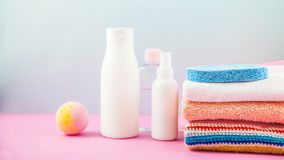 Bathroom accessories - towels, cream, bath foam and shampoos on a light, bright background Concept of caring for yourself, your bo. Bathroom accessories - towels Stock Images