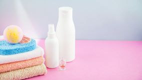 Bathroom accessories - towels and shampoos,bath foam, cream on a light, bright blue and pink background The concept of caring for. Yourself, your body. Place Stock Photos