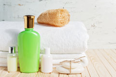 Bathroom accessories and white towel. Soap and lotion. Beauty care accessories for bath. White background. Copy space. Selective focus Stock Photos