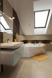 Bathroom in the attic. Modern bathroom with yellow additions in the attic Stock Photos