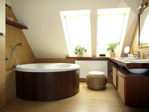 Bathroom in the attic. Cosy brown and white bathroom in the loft Stock Photos