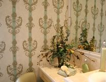 Bathroom with attractive wallpaper. And accessories in soft green and beige stock photos