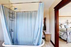 Bathroom with bath tub and blue curtain around it Stock Images