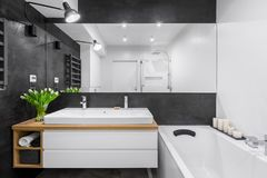 Bathroom with big mirror. Black and white bathroom with big mirror, bathtub, lighting and countertop double basin stock image