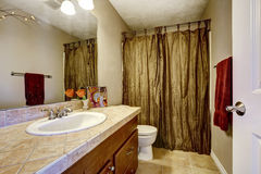 Bathroom with brown cabinet and mustard curtains Royalty Free Stock Photo
