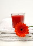 Bathroom Candle. Funky red bath candle for a relaxing romantic soak in the tub and red gerbera flower on clean white bath towel Stock Images