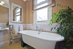 Bathroom with a contemporary bath tub. On wooden stands stock image