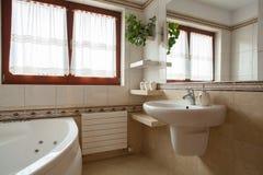 Bathroom corner. Interior of spacious beige bathroom, sink and bath Stock Photos