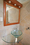A bathroom corner with a mirror and a glass sink bowl. An ideal bathroom supplies. Tempered and durable glass basin. The basin can be placed on the surface of Royalty Free Stock Image