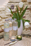 Bathroom decoration. A bathroom decorated with white tulips, three cosmetic oils and candles Stock Photos