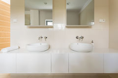 Bathroom designed for two. Light bathroom with white tiles, two basins and mirrors royalty free stock images