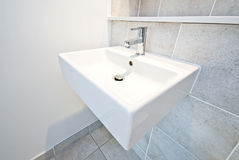 Bathroom detail ceramic wash basin. And natural stone tiled walls in beige Stock Image