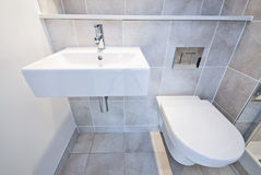 Bathroom detail with toilet and wash basin. Detail of a modern en suite bathroom with ceramic toilet, wash basin in beige Royalty Free Stock Photography